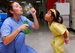 pediatric nurse playing with patient