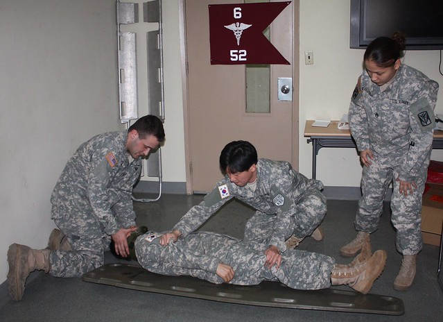 four military personnel performing first aid