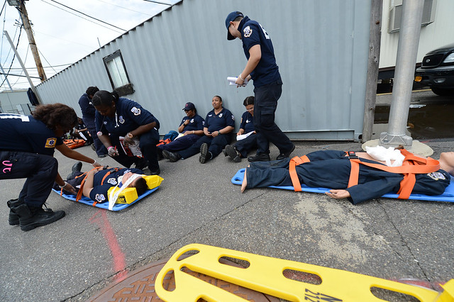person lying on medical stretchers with medical team around